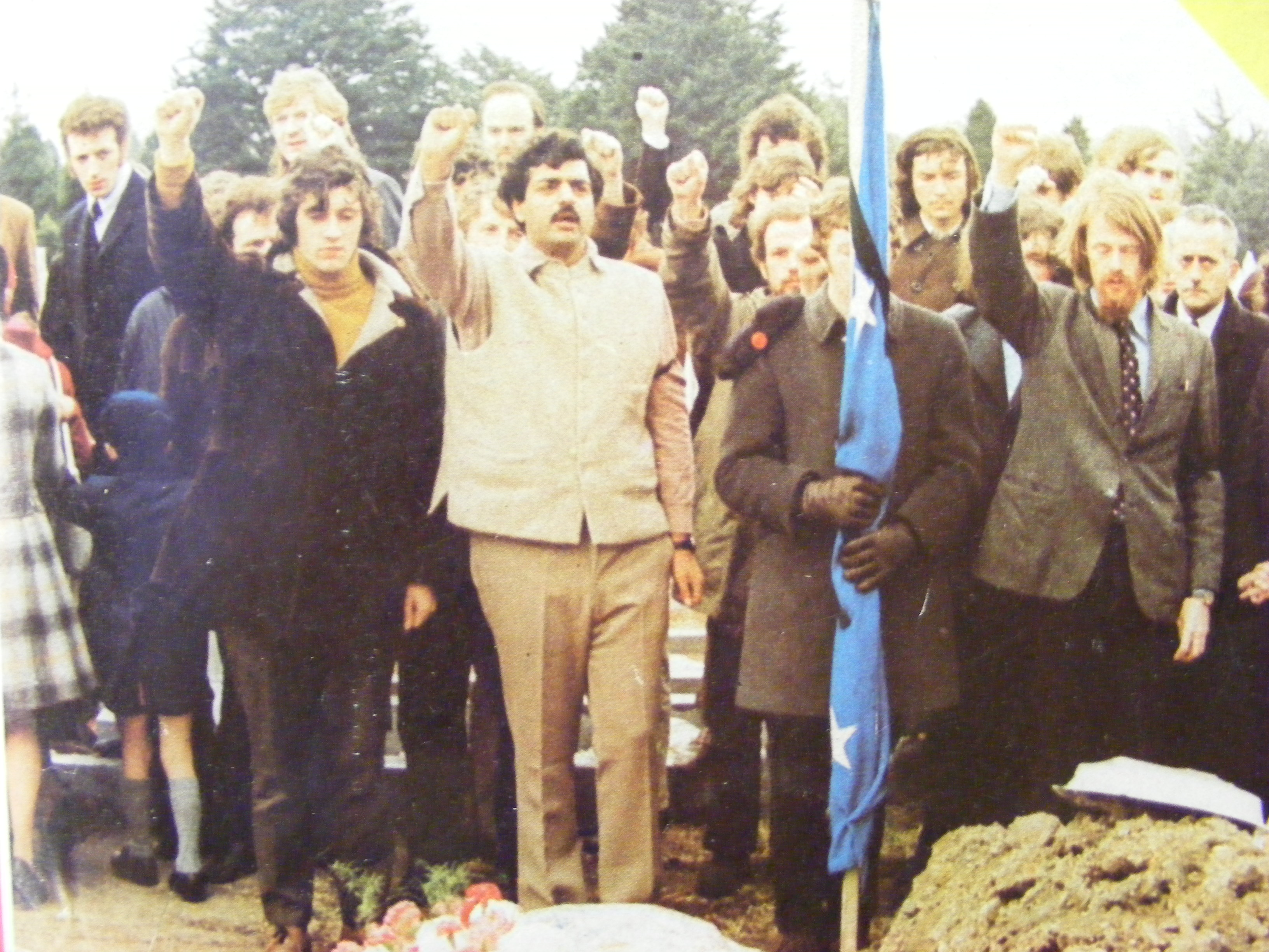 Charlie Bird and Tariq Ali giving a clenched fist salute at the graveside of assassinated Saor Éire leader, Peter Graham